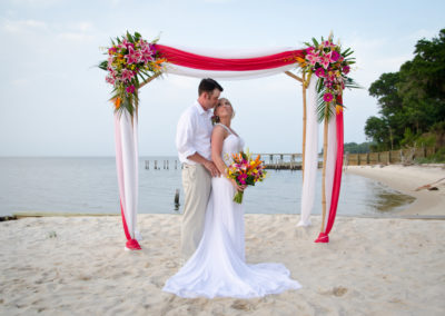 Bride and groom under the bamboo arbor at a beach wedding
