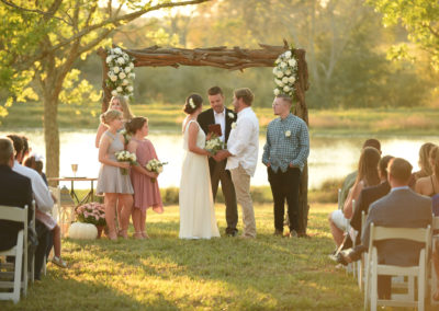 Driftwood arbor decorated with fresh floral arrangements